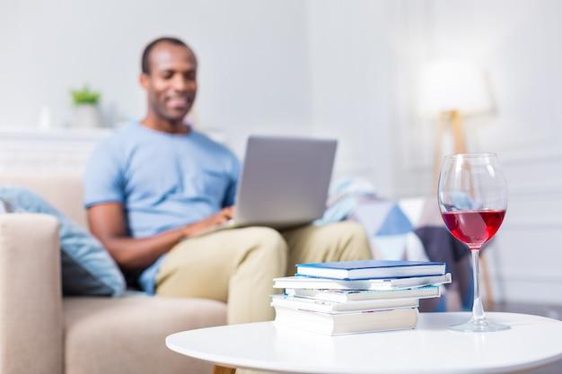 Селективный фокус бокала, наполненного вином, стоящего возле книг на журнальном столике