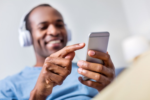 Селективный фокус современного смартфона, которым пользуется позитивный симпатичный приятный мужчина во время прослушивания музыки