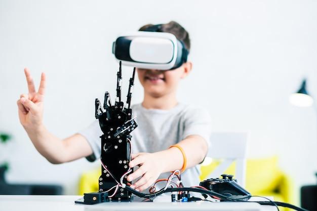 テーブルの上に立っているロボットの手の選択的な焦点、それを実験している前向きな独創的な少年