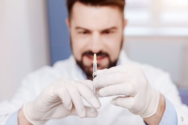 주사를하는 동안 전문적인 좋은 찾고 남성 의사에 의해 개최되는 주사기의 선택적 초점