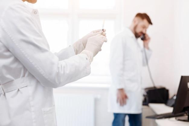의사의 손에있는 동안 약으로 가득 찬 주사기의 선택적 초점과 사용 준비