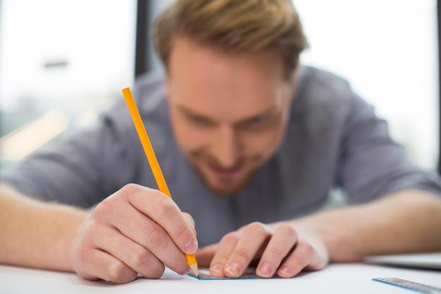 전문적인 그림을 그리는 동안 좋은 즐거운 기뻐하는 사람이 사용하는 노란색 연필의 선택적 초점