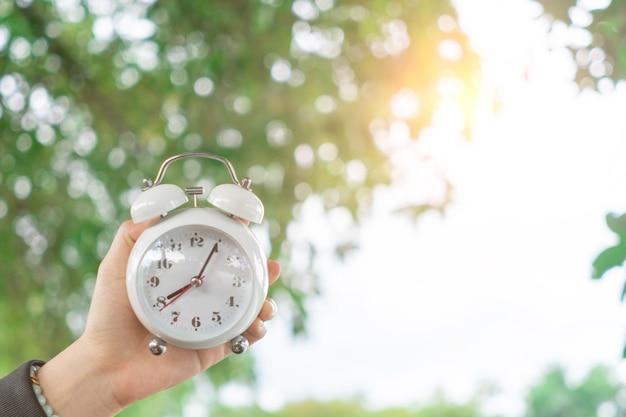 자연 보케 배경으로 알람 시계의 선택적 초점. 라이프 스타일 생산적인 삶의 개념입니다.
