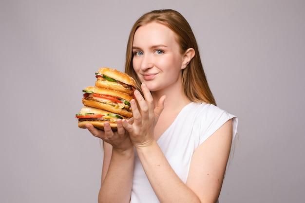 회색 외진 배경에 놀란 소녀의 손에 있는 크고 맛있는 햄버거의 선택적 초점. 카메라를 보고 맛있는 패스트 푸드를 먹는 큰 눈을 가진 충격을 받은 여자. 크기와 음식의 개념입니다.