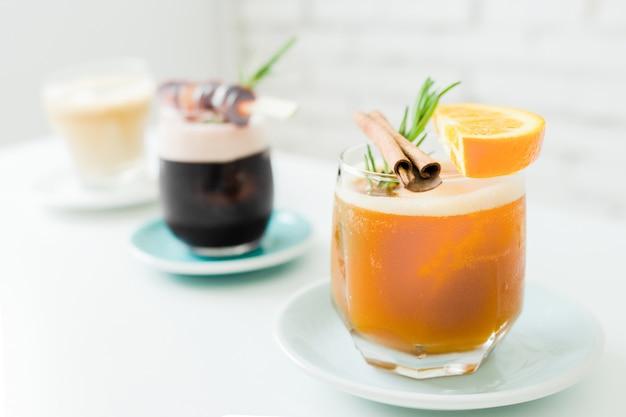 グラスにフルーツとカクテルやモクテルのセレクティブフォーカス。ビンテージのレストランでオレンジとブドウの伝統的な夏のアルコールカクテル