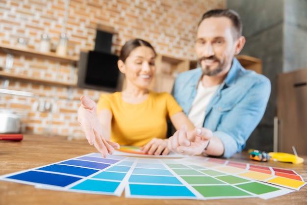 陽気な幸せな陽気なカップルがそれを指して笑っている間、表面に横たわっているカラーサンプルの選択的な焦点
