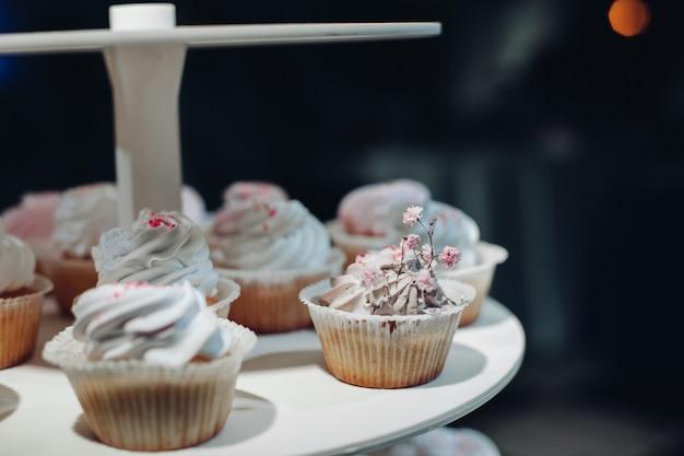 プレートで提供されるかわいいおいしいカップケーキの選択的な焦点。テーブルの上にとどまるクリームとおいしいデザートのクローズアップ。結婚式のキャンディーバー、デザート、菓子のコンセプト。