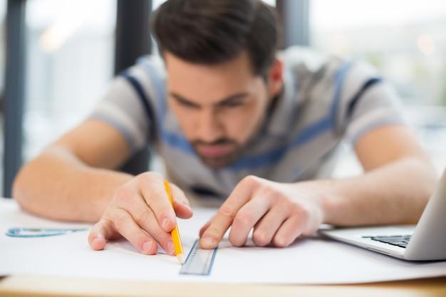 일하는 동안 똑똑한 잘 생긴 멋진 엔지니어가 사용하는 그리기 도구의 선택적 초점