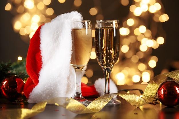 Селективный фокус бокалов, полных шампанского на фоне рождественских огней