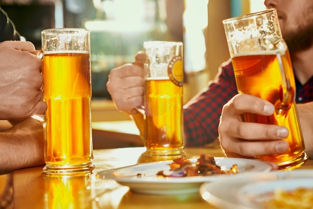 술집에서 테이블에 맥주 서 안경의 선택적 초점. 파인트를 지키고, 맥주를 마시고, 스낵을 먹고, 술집에서 이야기하는 강한 남성 회사. 음료와 알코올의 개념.