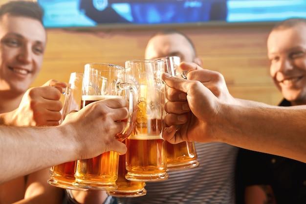 술집에서 쾌활 한 남자 친구의 손에 맥주 잔의 선택적 초점. 술을 마시고 술집에서 토스트하는 남성 회사. 행복과 음료의 개념.
