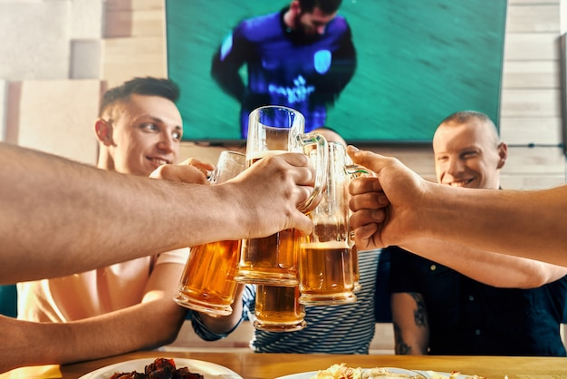 맥주 잔을 들고 카페에서 토스트하는 행복한 강한 남자의 선택적 초점