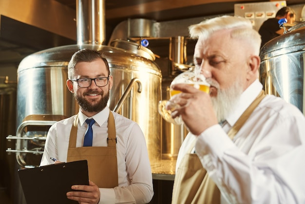 フォルダーを保持し、笑顔で同僚を見ている幸せな若い醸造者の選択的な焦点。ビールのグラスを保持し、おいしいゴールデンエールを味わう男。生産と飲酒の概念。