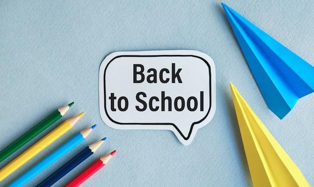 Селективный фокус стекла лупы и текста «снова в школу 2021» с красочной ручкой на фоне белой школьной книги.