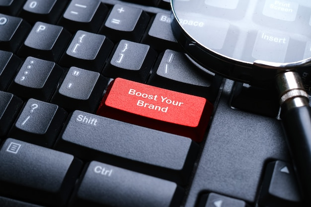 Селективный фокус увеличительного стекла на клавиатуре компьютера с красной кнопкой, написанной с помощью boost your brand. бизнес и финансовая концепция.