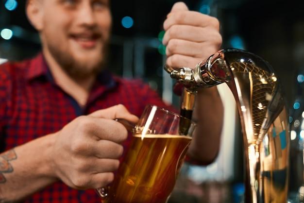 파인트를 유지하고 술집에서 맥주를 붓는 남성 손의 선택적 초점. 문신 작업과 바에서 사람들을 서비스하는 체크 무늬 셔츠에 젊은 수염 바텐더. 에일과 직업의 개념.