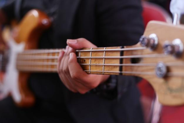 Избирательный фокус человека, играющего на гитаре на басу