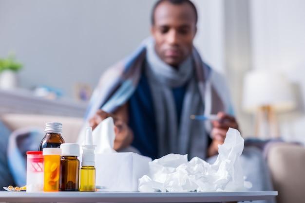 ティッシュペーパーの近くのベッドサイドテーブルに立っている薬の選択的な焦点
