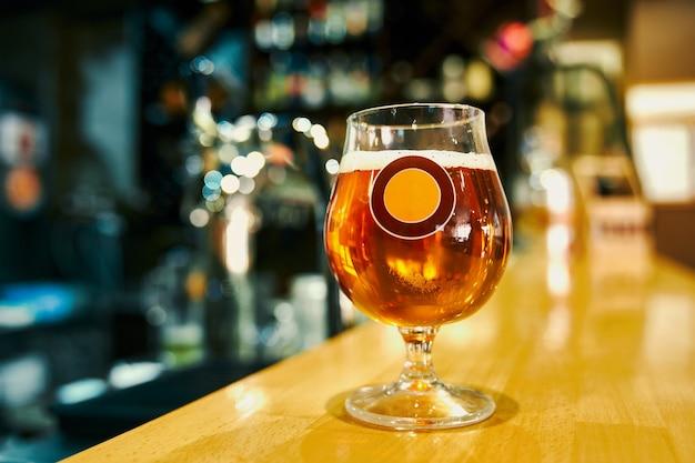 술집에서 테이블에 서있는 맛있는 시원한 맥주 머그잔의 선택적 초점. 바에서 고객을위한 frech 알코올 음료. 카페에서 저녁에 카운터에 서있는 맥주의 파인트. 음료와 양조장의 개념.
