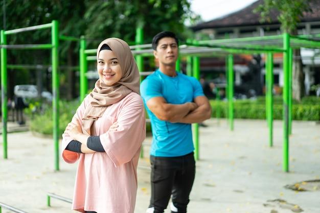 公園で運動しながら交差した手で背中合わせに立っている間笑顔のイスラム教徒のカップルの選択的な焦点