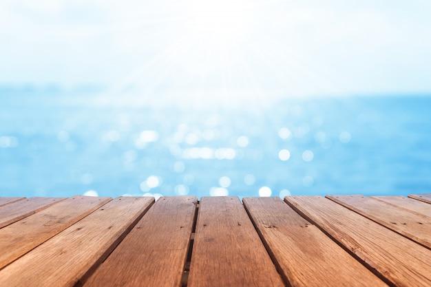 Селективный фокус старой деревянной таблицы с красивой предпосылкой пляжа для дисплея вашего продукта.