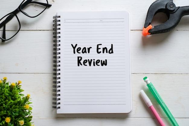 흰색 나무 배경에 2020년 리뷰로 작성된 펜, 안경 및 노트북의 선택적 초점.