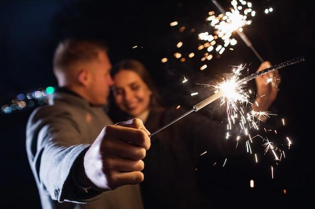 屋外で休日の時間を楽しんでいる若いカップルの手に線香花火の選択的な焦点。