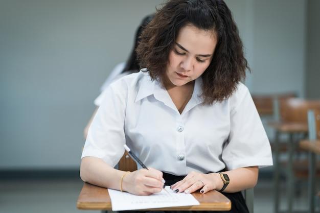 10代の大学生の選択的な焦点は、講義の椅子に座り、最終試験室または教室で受験用紙の解答用紙に書き込みます。教室で制服を着た大学生。