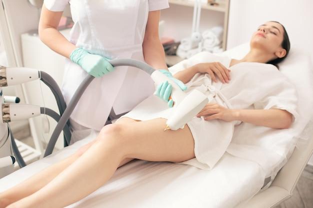 젊은 여성의 다리에 있는 혈관망을 제거하는 현대적인 도구로 손의 선택적 초점