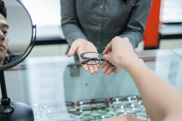Селективный фокус рук продавца, отдающего очки в руки покупателю в оптике