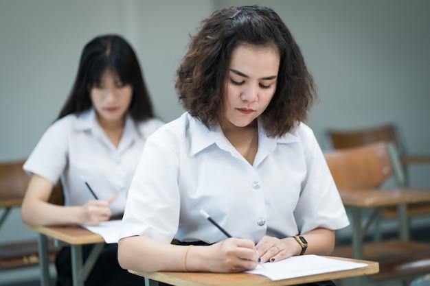 教室の講義椅子に座っている10代の大学生の選択的な焦点は、最終試験テストを行う際に試験紙の解答用紙に書き込みます。学生服を着た女子学生。