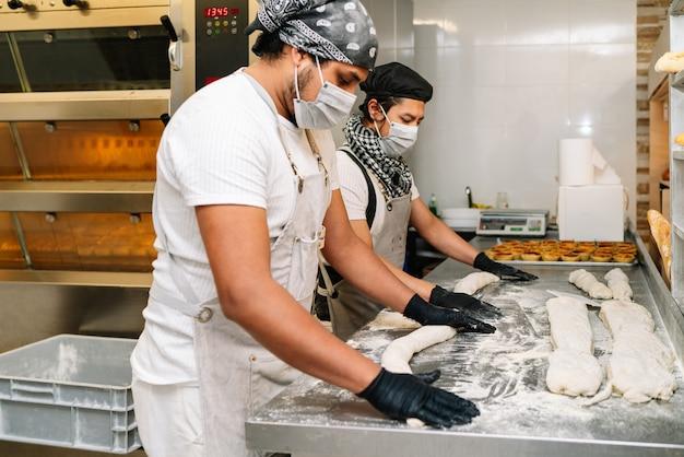 얼굴 마스크와 장갑을 끼고 빵 반죽을 반죽하는 두 라틴계 빵 굽는 사람의 선택적 초점