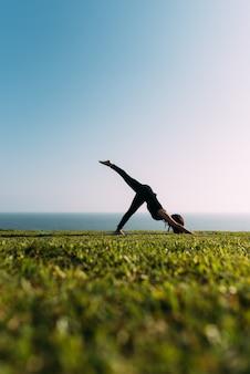ヨガをしている女性の選択的な焦点。屋外で運動するヨガの先生