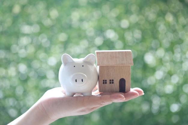 자연 녹색 배경, 사업 투자 및 부동산 개념에 모델 하우스와 함께 돼지를 들고 여자 손의 선택적 초점
