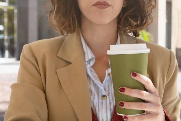 이동하기 위해 커피를 들고 있는 여성의 손에 대한 선택적 초점, 직장에서의 개념 휴식, 복사 공간.