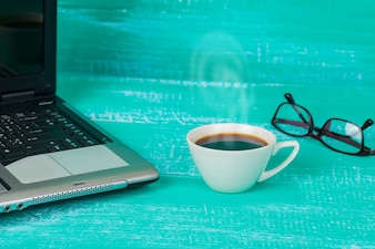 Selective focus office table : eyeglass , laptop, note book and cup on the wooden