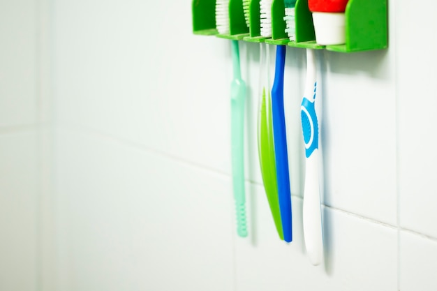 Selective focus oftoothbrush group hanging on the bathroom wall