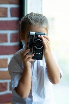 Селективный фокус, старый фотоаппарат в руках девушки, сидящей на подоконнике