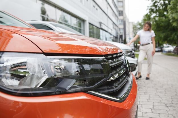 야외 주차장에서 자동차에 선택적 초점, 판매를 위해 자동차를 검사하는 여자