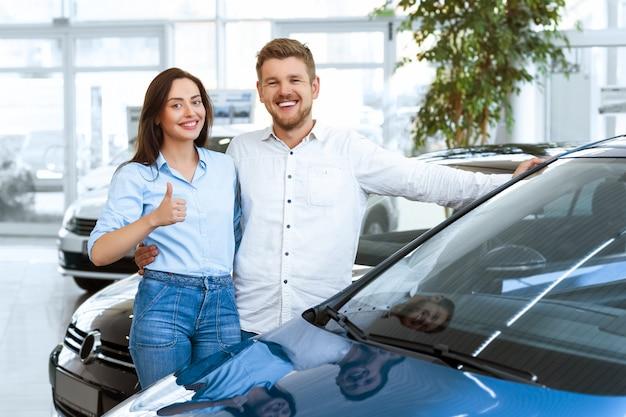 Селективный акцент на автомобиль молодая пара, выбирая автомобиль для покупки в салоне автомобиля на заднем плане