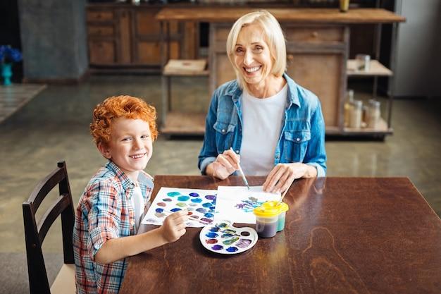 Селективный фокус на кудрявом маленьком художнике, сидящем рядом со своей бабушкой, который рисует и смотрит в камеру с веселыми улыбками на лицах.