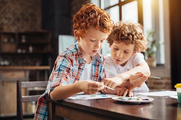 Селективный акцент на рыжем мальчике, сидящем рядом со своим старшим братом и выбирающем цвет краски из палитры, одновременно болтая и рисуя вместе за столом.
