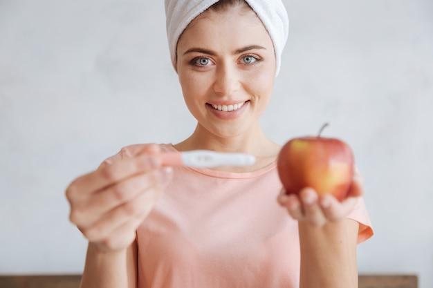 Селективный фокус на сероглазой женщине неземной красоты, улыбающейся, держащей тест на беременность и яблоко кокса