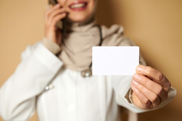 電話で話しているヒジャーブを身に着けている女性のイスラム教徒の医師の手にあるプラスチックの空白の白いカードに選択的に焦点を当てる