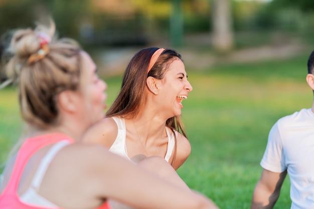 Избирательный фокус на смеющейся женщине, сидящей в парке с друзьями