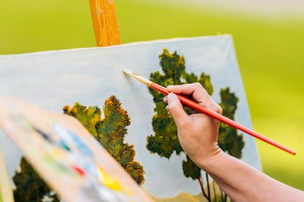 캔버스에 브러시로 여성의 손 그림에 선택적 초점