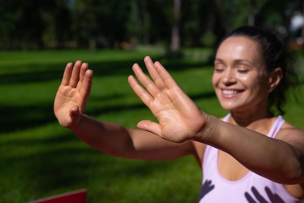 일광욕을하고 공원에서 화창한 날을 즐기는 동안 웃는 여자에 대한 선택적 초점