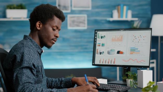 Селективный акцент на афро-американском мужчине, работающем из дома, делая заметки в блокноте