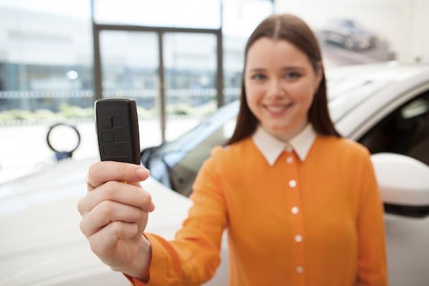 Селективное внимание на ключ от машины счастливая молодая женщина держит, ее новый автомобиль на фоне