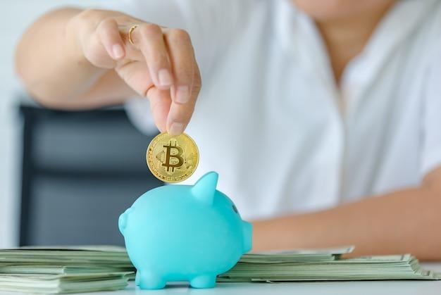 Селективный акцент на монете, руке, держащей символ биткойн-денег, и положил ее в копилку для сохранения. концепция сокровищ криптовалюты и инвестиций в будущее.